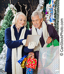 Senior Couple Using Digital Tablet At Christmas Store -...