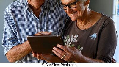 Senior couple using digital tablet in kitchen 4k