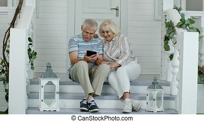 Senior couple using digital tablet in porch at home. Watching funny videos on social media network