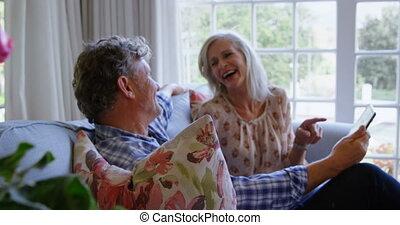 Senior couple using digital tablet on sofa 4k