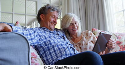 Senior couple using digital tablet on sofa 4k - Happy senior...