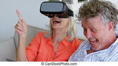 Senior couple using laptop and virtual reality headset on...