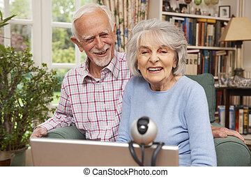 Senior Couple Using Laptop And Webcam To Talk To Family
