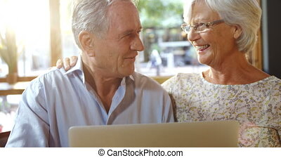 Senior couple using laptop in cafe 4k