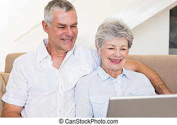 Senior couple using laptop on sofa