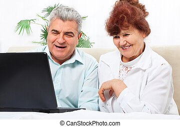 senior couple using laptop sitting sofa