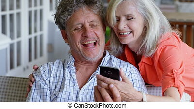 Senior couple using mobile phone on the porch 4k - Happy...