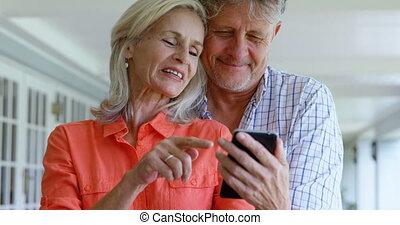 Senior couple using mobile phone on the porch 4k - Senior...