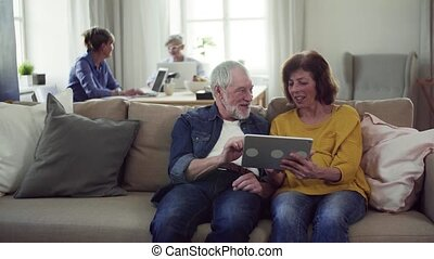 Senior couple using tablet in community center club.
