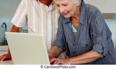 Senior couple using the laptop at t - Senior couple using...