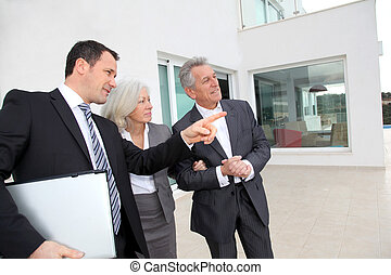 Senior couple visiting luxury villa with real-estate agent