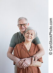 Vertical portrait of loving senior couple embracing and looking at camera while standing against white background