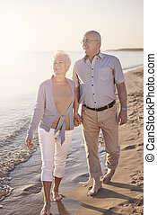 Senior couple walking across the beach