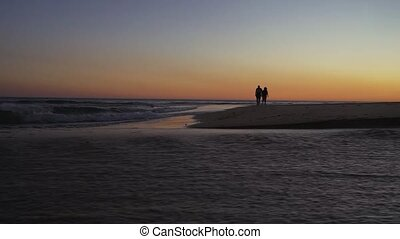 Senior couple walking along coast.