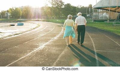 Senior couple walking along the running track - Senior...