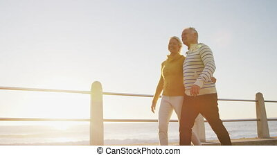 Senior couple walking alongside beach - Happy retired senior...