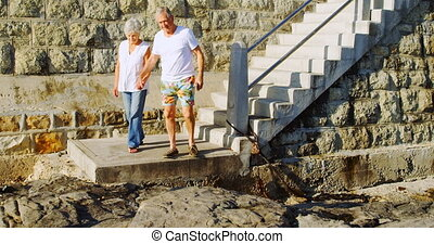 Senior couple walking downstairs near beach 4k