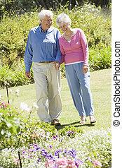 Senior couple walking in garden admiring flowerbeds