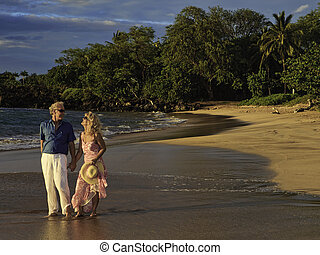senior couple walking on a maui beach