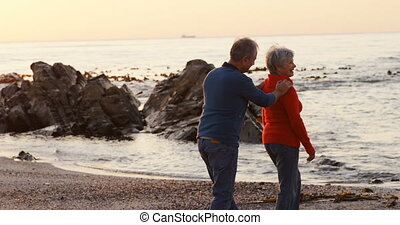 Senior couple walking on beach 4k