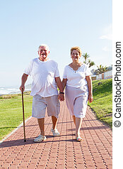 senior couple walking on beach front - husband using cane