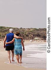 senior couple walking on the beach