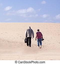 Senior couple walking on the sand.
