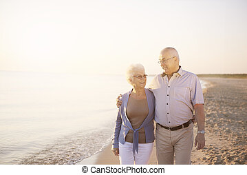 Senior couple walking on the summer beach