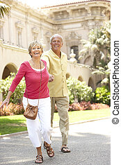Senior Couple Walking Through City Street