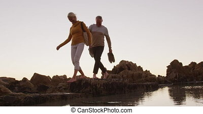 Senior couple walking while holding hands at beach