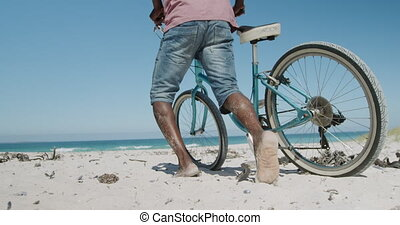 Senior couple walking with a bike at the beach