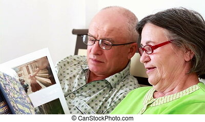 Senior couple watching a photo album full of memories, while lying in bed in the morning.
