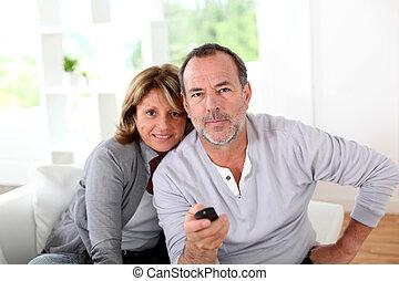 Senior couple watching television at home