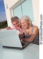 Senior couple waving at webcamera on laptop computer