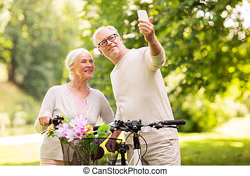 senior couple with bicycles taking selfie at park