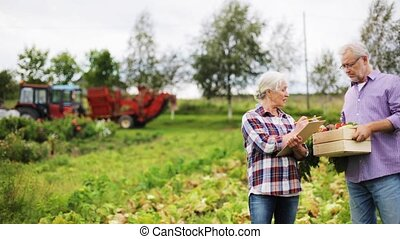 farming, gardening, harvesting, and people concept - senior couple with box of vegetables and clipboard on farm or garden