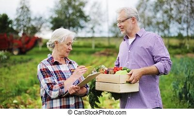 senior couple with box of vegetables on farm