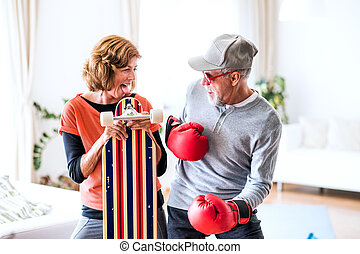 Senior couple with boxing gloves and longboard having fun at...