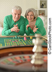 Senior couple with casino chips