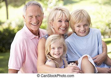 Senior couple with children posing in park