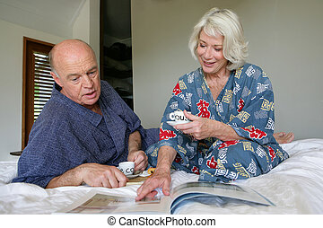 Senior couple with coffee in bed