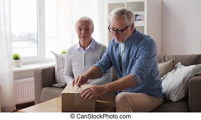 senior couple with delivery note opening parcel - delivery,...