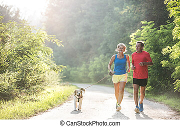 Senior couple with dog running in green sunny nature -...