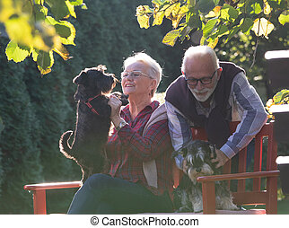 Senior couple with dogs in garden