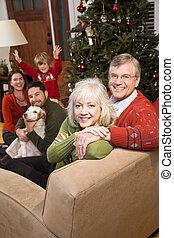 Senior couple with family by Christmas tree - three...