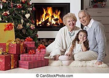 Senior couple with granddaughter enjoying Christmas