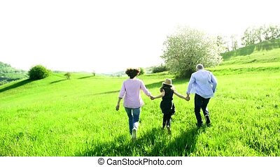 Senior couple with granddaughter outside in spring nature,...