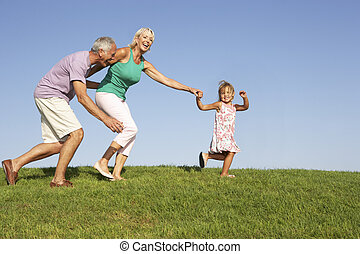 Senior couple, with granddaughter,  running though field
