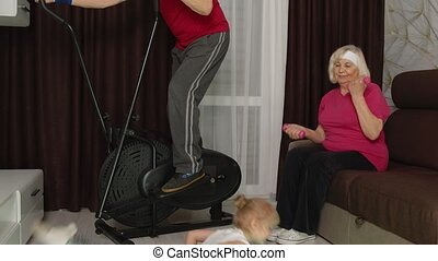 Senior elderly couple man woman with child girl using orbitrek, doing weight lifting sport dumbbells and stretching exercises training at home. Active old grandparents with granddaughter working out