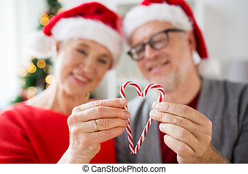 senior couple with heart of christmas candy canes -...